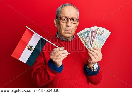 Handsome senior man with grey hair holding egypt flag and egyptian pounds banknotes relaxed with serious expression on face. simple and natural looking at the camera.
