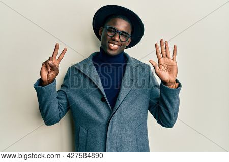 Young african american man wearing elegant style showing and pointing up with fingers number seven while smiling confident and happy.