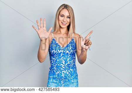 Young beautiful caucasian woman wearing summer dress showing and pointing up with fingers number seven while smiling confident and happy.