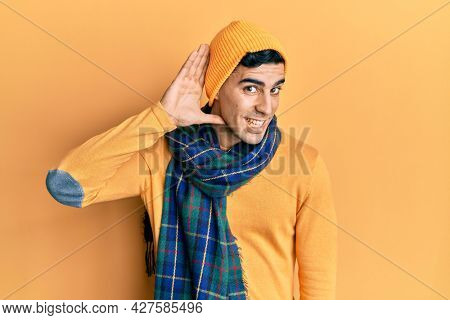 Handsome hispanic man wearing wool hat and winter scarf smiling with hand over ear listening an hearing to rumor or gossip. deafness concept.