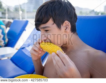 Boy sitting on beach pier and eating