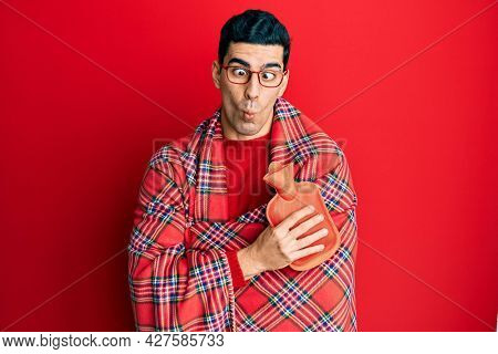 Handsome hispanic man wrapped in a winter blanket holding hot water bag making fish face with mouth and squinting eyes, crazy and comical.
