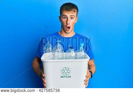 Young caucasian man holding recycling wastebasket with plastic bottles afraid and shocked with surprise and amazed expression, fear and excited face.