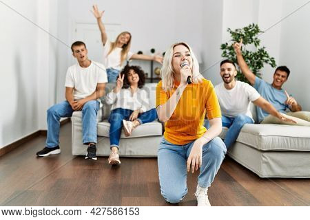 Group of young friends having party singing song using microphone at home.