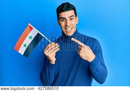 Handsome hispanic man holding syria flag smiling happy pointing with hand and finger