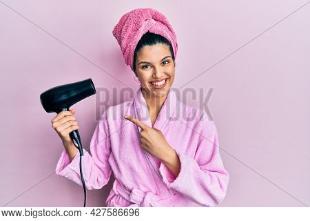 Young hispanic woman wearing shower bathrobe using dryer smiling happy pointing with hand and finger