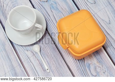 Plastic Yellow Lunch Box And Cup With Saucer On Wooden Background.