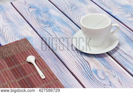 Porcelain Cup With Saucer And Bamboo Napkin On Wooden Background.