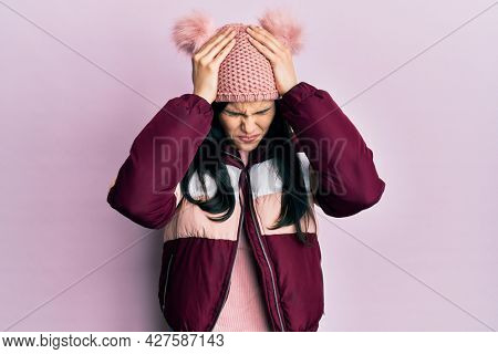 Young hispanic woman wearing wool winter sweater and cap suffering from headache desperate and stressed because pain and migraine. hands on head.
