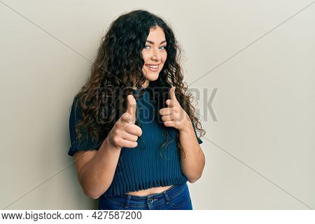 Young brunette woman with curly hair wearing casual clothes pointing fingers to camera with happy and funny face. good energy and vibes.
