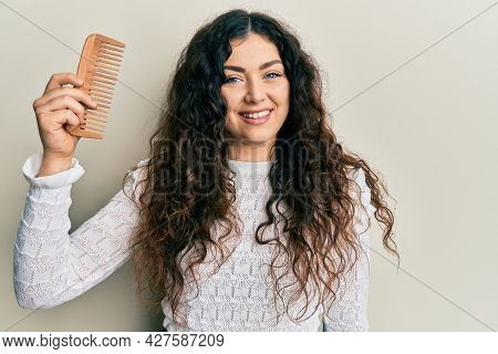 Young brunette woman with curly hair styling hair using comb looking positive and happy standing and smiling with a confident smile showing teeth