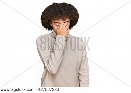 Young hispanic girl wearing wool winter sweater tired rubbing nose and eyes feeling fatigue and headache. stress and frustration concept.
