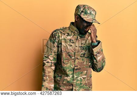Young african american man wearing army uniform smelling something stinky and disgusting, intolerable smell, holding breath with fingers on nose. bad smell