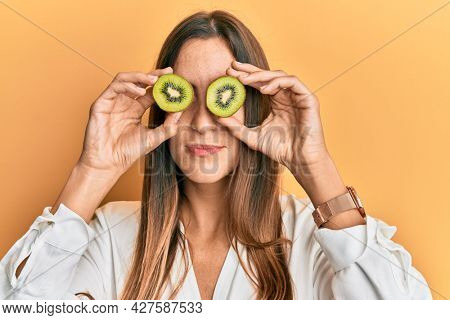 Young beautiful woman holding slice of kiwi over eyes relaxed with serious expression on face. simple and natural looking at the camera.