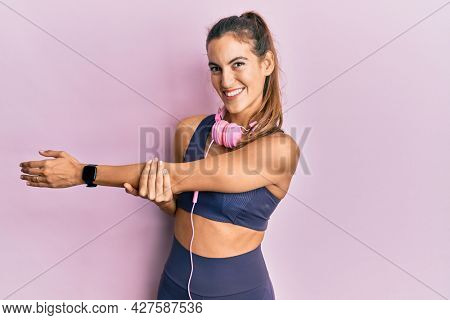 Young sportswoman stretching muscles after doing exercise wearing sporty clothes and headphones, standing doing flexibility activity