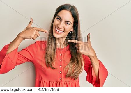 Young beautiful woman wearing casual clothes smiling cheerful showing and pointing with fingers teeth and mouth. dental health concept.