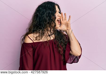 Young brunette woman with curly hair wearing casual clothes shouting and screaming loud to side with hand on mouth. communication concept.