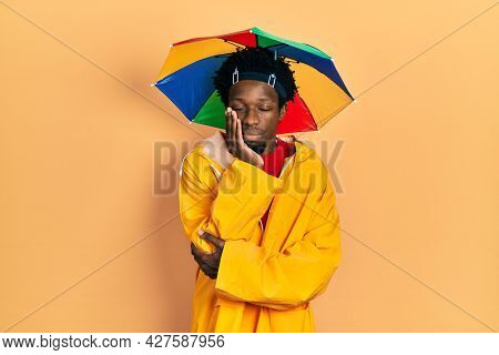 Young african american man wearing yellow raincoat thinking looking tired and bored with depression problems with crossed arms.