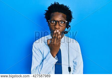Young african american man wearing call center agent headset covering mouth with hand, shocked and afraid for mistake. surprised expression