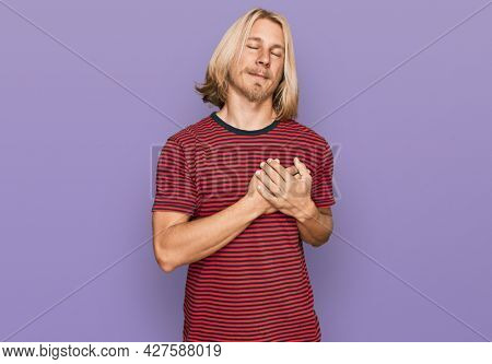 Caucasian man with blond long hair wearing casual striped t shirt smiling with hands on chest with closed eyes and grateful gesture on face. health concept.