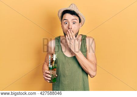 Young hispanic man wearing summer hat drinking mojito covering mouth with hand, shocked and afraid for mistake. surprised expression