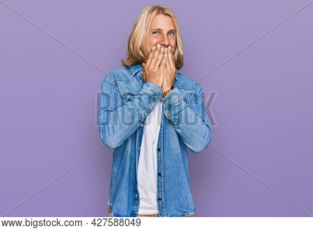 Caucasian man with blond long hair wearing casual denim jacket laughing and embarrassed giggle covering mouth with hands, gossip and scandal concept