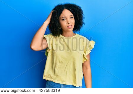 Young african american girl wearing casual clothes confuse and wonder about question. uncertain with doubt, thinking with hand on head. pensive concept.