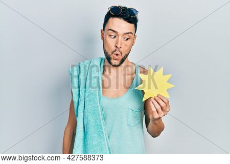 Young hispanic man wearing summer style holding yellow sun scared and amazed with open mouth for surprise, disbelief face