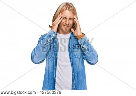 Caucasian man with blond long hair wearing casual denim jacket with hand on head, headache because stress. suffering migraine.