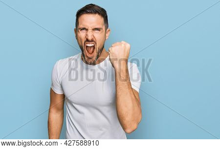 Handsome man with beard wearing casual white t shirt angry and mad raising fist frustrated and furious while shouting with anger. rage and aggressive concept.