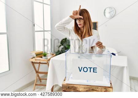 Hispanic business woman voting putting envelop in ballot box making fun of people with fingers on forehead doing loser gesture mocking and insulting.