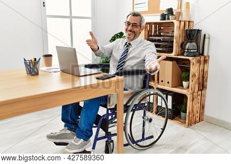 Middle age hispanic man working at the office sitting on wheelchair looking at the camera smiling with open arms for hug. cheerful expression embracing happiness.