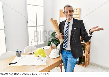Middle age hispanic business man holding paper blueprints smiling cheerful presenting and pointing with palm of hand looking at the camera.