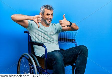 Handsome middle age man with grey hair sitting on wheelchair doing thumbs up and down, disagreement and agreement expression. crazy conflict