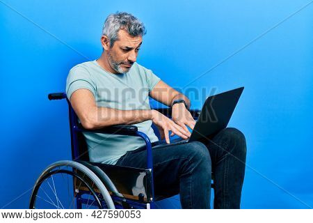 Handsome middle age man with grey hair sitting on wheelchair using laptop skeptic and nervous, frowning upset because of problem. negative person.