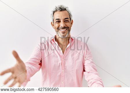Middle age hispanic man standing over isolated background looking at the camera smiling with open arms for hug. cheerful expression embracing happiness.