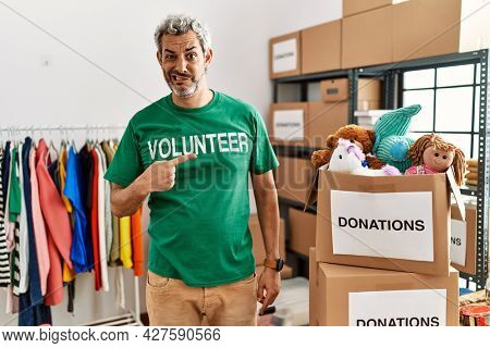 Middle age hispanic man wearing volunteer t shirt at donations stand pointing aside worried and nervous with forefinger, concerned and surprised expression