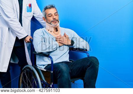 Handsome middle age man with grey hair on wheelchair wearing cervical collar smiling with hands on chest with closed eyes and grateful gesture on face. health concept.