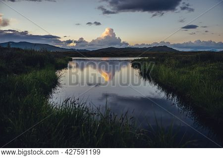 Scenic Sunset Landscape With Yellow Big Cloud In Form Of Explosion Above Mountain Lake. Awesome Gian
