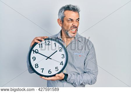 Handsome middle age man with grey hair holding big clock angry and mad screaming frustrated and furious, shouting with anger. rage and aggressive concept.