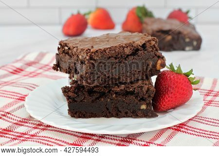 Two Stacked Chocolate Walnut Fudge Brownies, Macro, With Strawberries.  Macro, Selective Focus.
