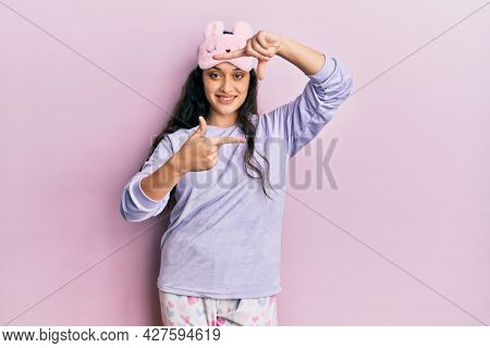 Beautiful middle eastern woman wearing sleep mask and pajama smiling making frame with hands and fingers with happy face. creativity and photography concept.