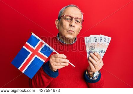 Handsome senior man with grey hair holding iceland flag and icelandic krona banknotes looking at the camera blowing a kiss being lovely and sexy. love expression.