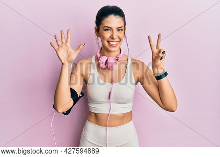 Young hispanic woman wearing gym clothes and using headphones showing and pointing up with fingers number seven while smiling confident and happy.