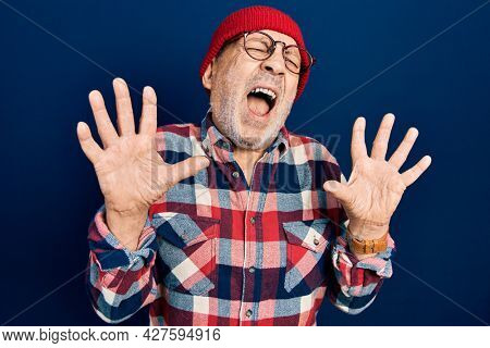 Handsome mature man wearing hipster look with wool cap crazy and mad shouting and yelling with aggressive expression and arms raised. frustration concept.