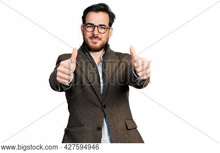 Young hispanic man wearing business jacket and glasses approving doing positive gesture with hand, thumbs up smiling and happy for success. winner gesture.