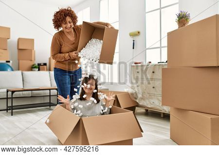 Mature mother and down syndrome daughter moving to a new home, having fun with cardboard foam