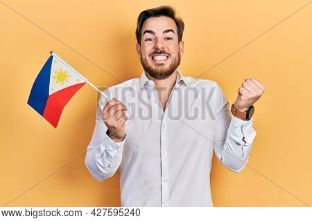 Handsome caucasian man with beard holding philippines flag screaming proud, celebrating victory and success very excited with raised arm