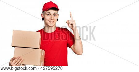 Young caucasian boy with ears dilation holding delivery package smiling with an idea or question pointing finger with happy face, number one