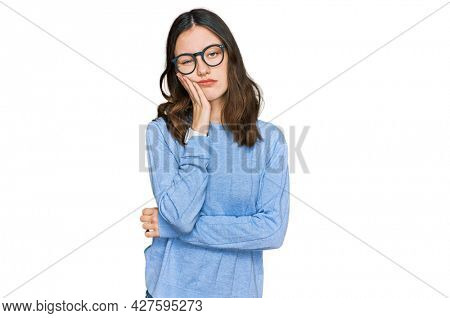 Young beautiful woman wearing casual clothes and glasses thinking looking tired and bored with depression problems with crossed arms.
